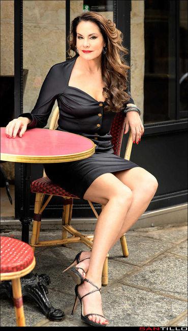 Dominatrix Gweneth profesional en café en vestido negro y tacones altos